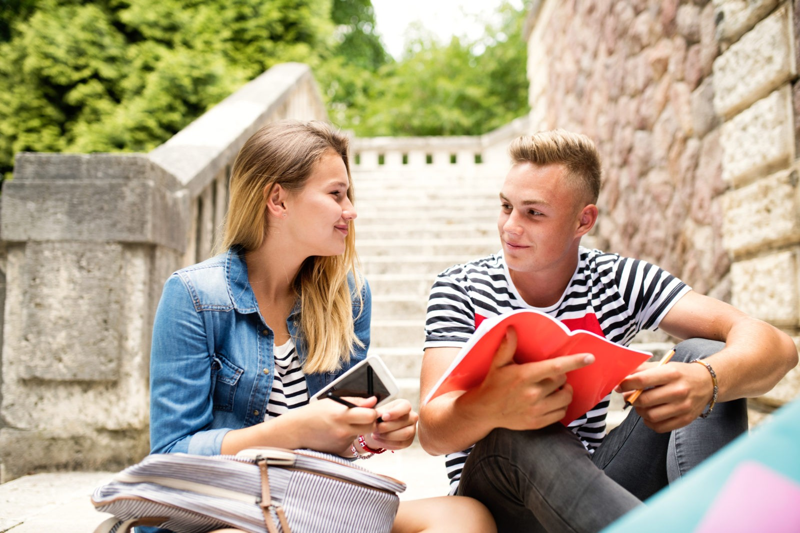 Teenage student couple in front of university studying