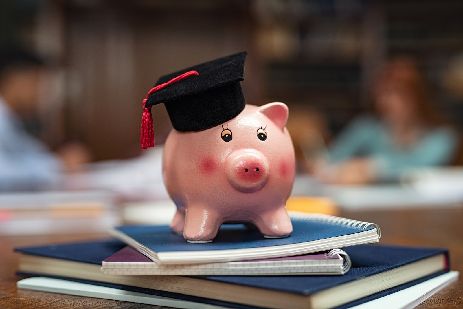 How long does it take to pay off student loans: Piggy bank with graduation cap