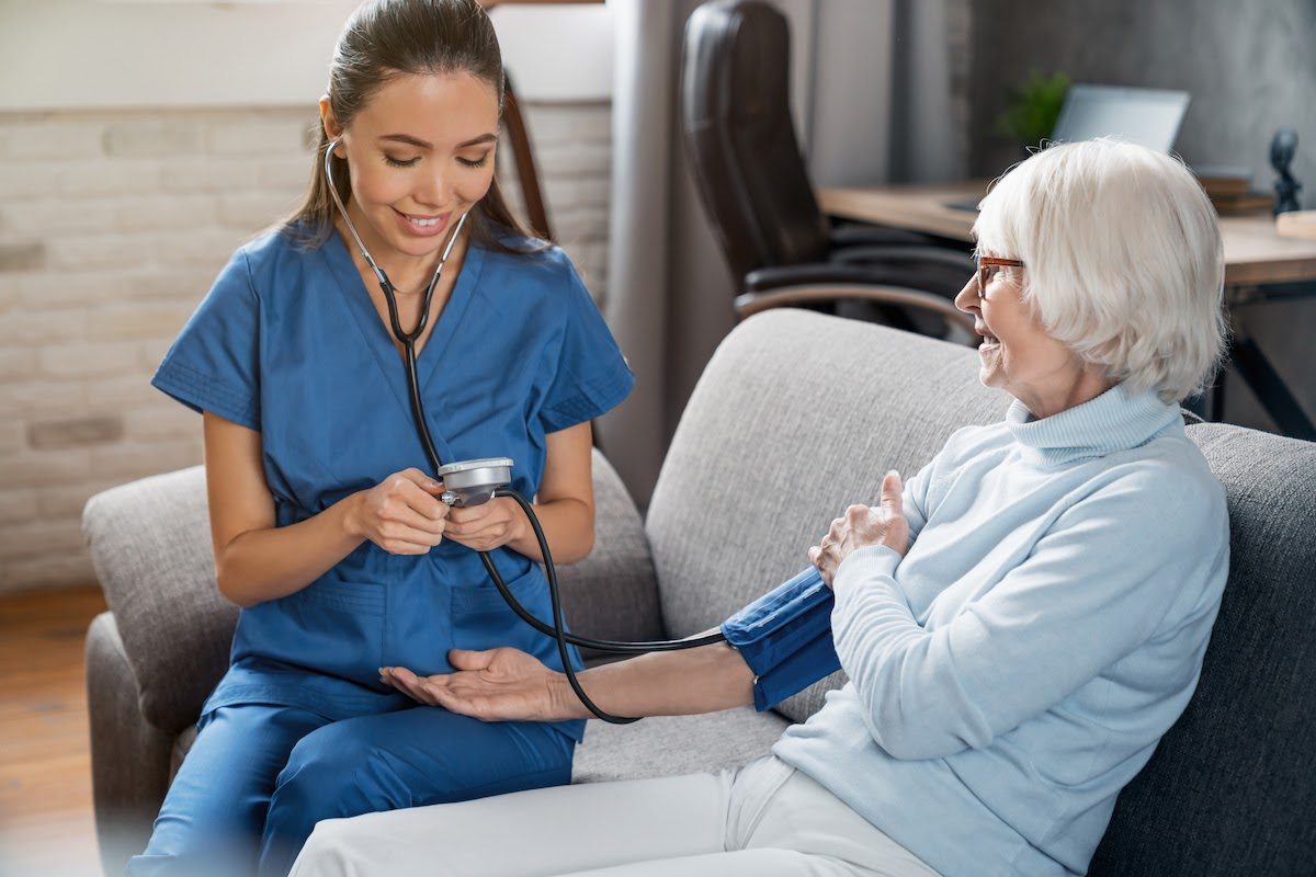 What Is a Major in College: Student nurse taking blood pressure of an old lady