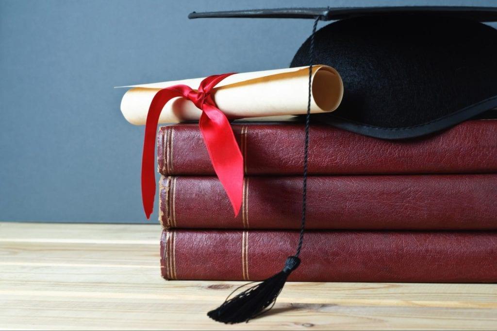 Toga hat, diploma and books