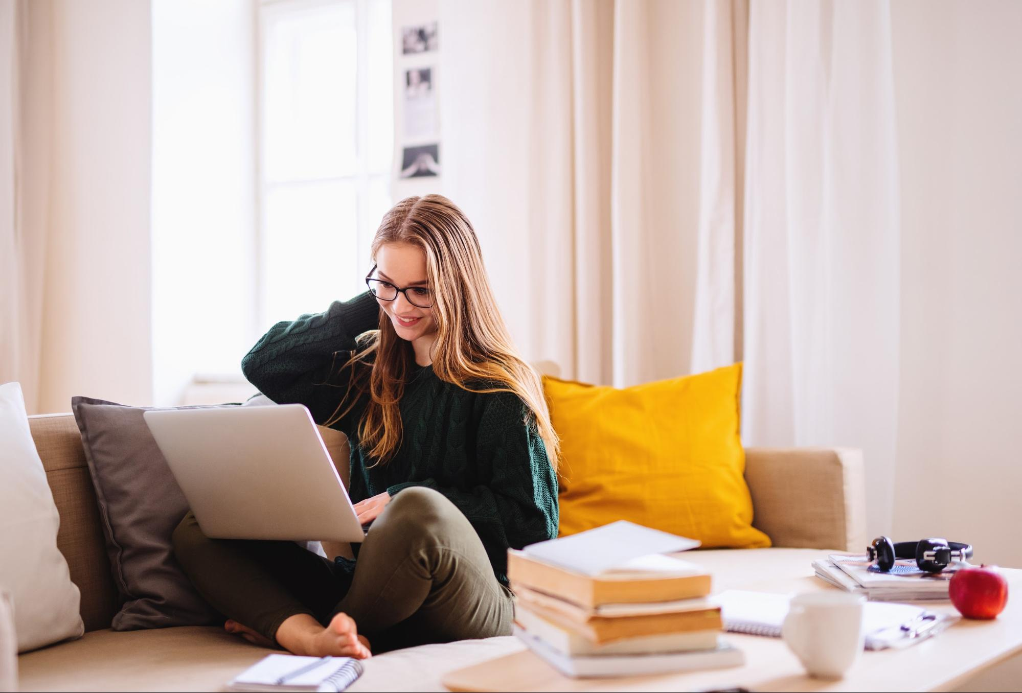 Associate's degree: A young female student using a laptop while sitting on a sofa